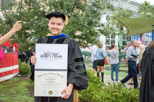 Richard Thripp Holding Diploma Outside, 2nd Photo