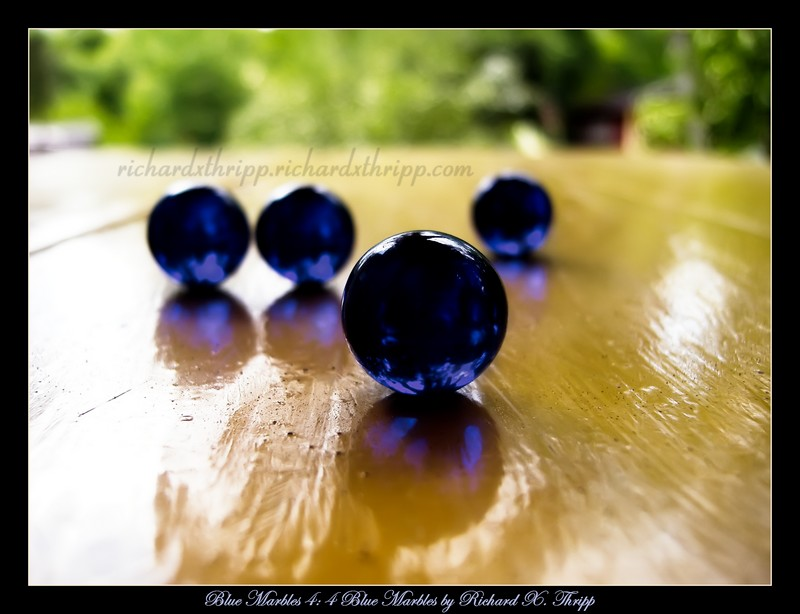 Blue Marbles 4: 4 Blue Marbles — light, reflections, and spacing make for three-dimensional orbs
