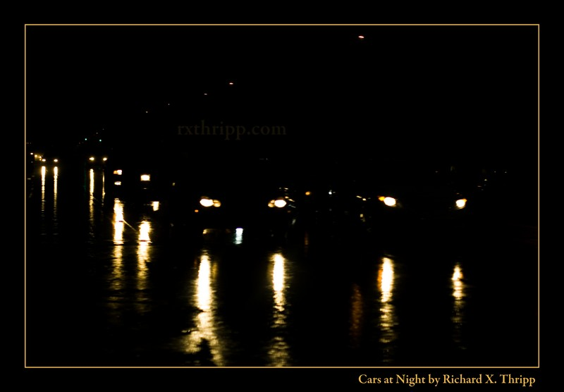Cars at Night — a slick road reflecting the headlights of cars