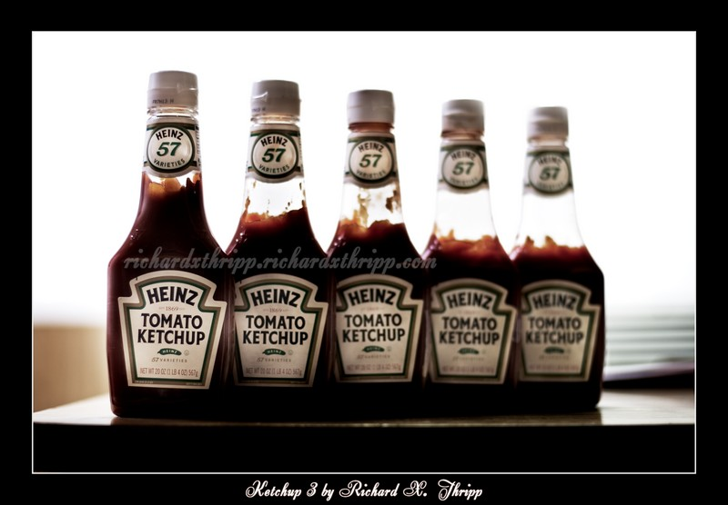 Ketchup 3 — a row of black ketchup bottles
