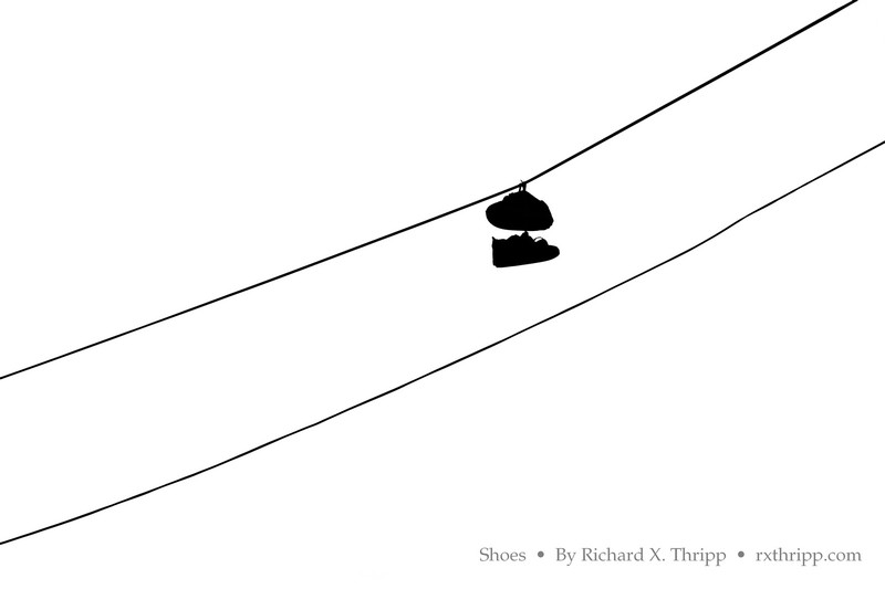 Shoes — hanging by a shoestring, from the power lines
