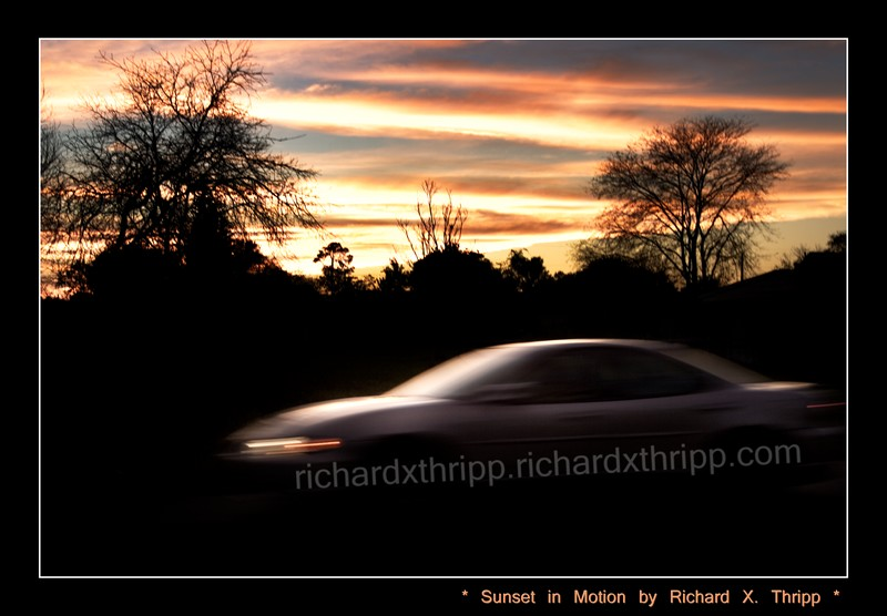 Sunset in Motion — a car speeding past a bright-orange sunset