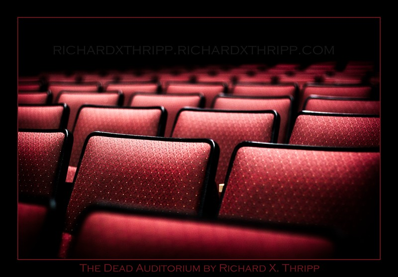 The Dead Auditorium — empty red chairs in a dark theater