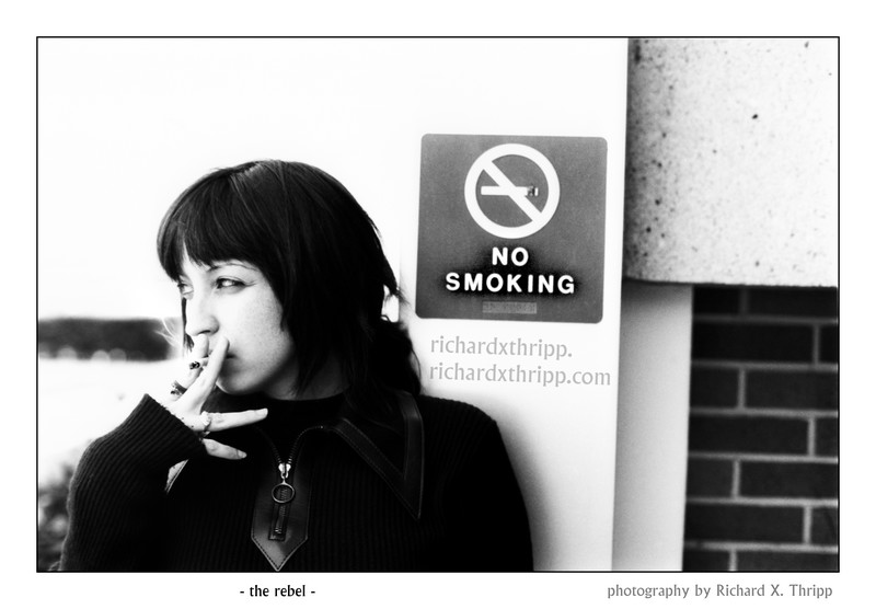 The Rebel — a girl smoking in front of a no-smoking sign (shameful!)