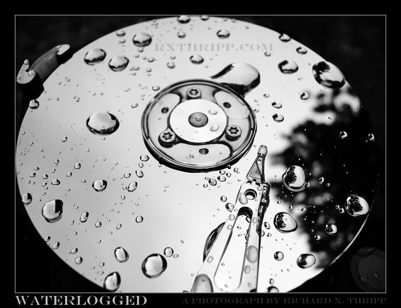 Waterlogged — a hard disk platter and arm, dotted with raindrops